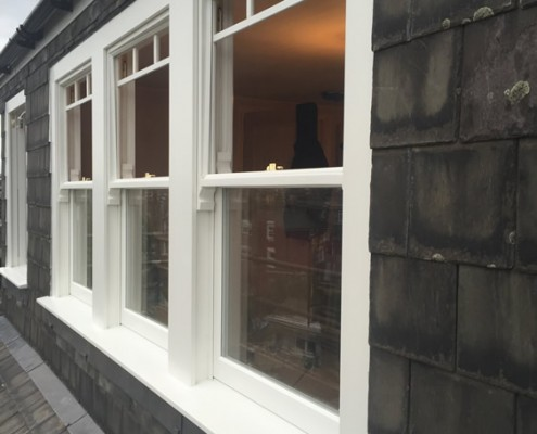 Three white timber sash windows exterior
