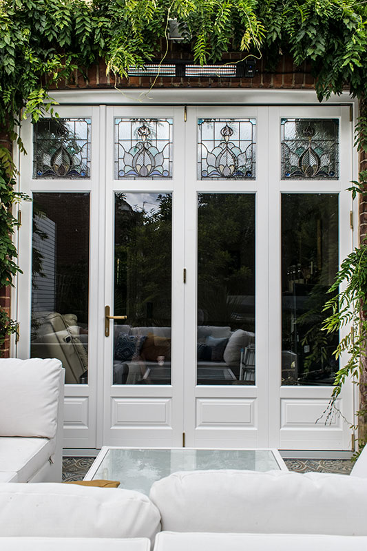 Timber bifold doors with stained glass windows in finchley for North windows and doors