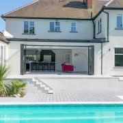 Black bifold doors onto swimming pool