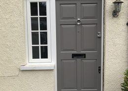 Grey timber door with glazing