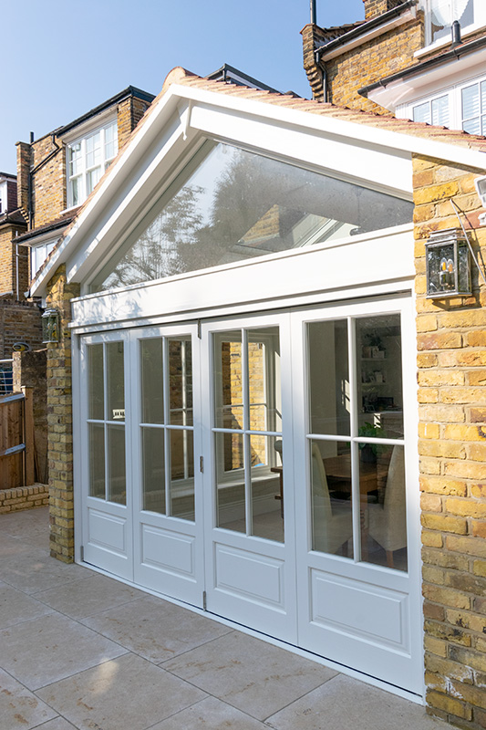 White timber bifold doors with apex window above