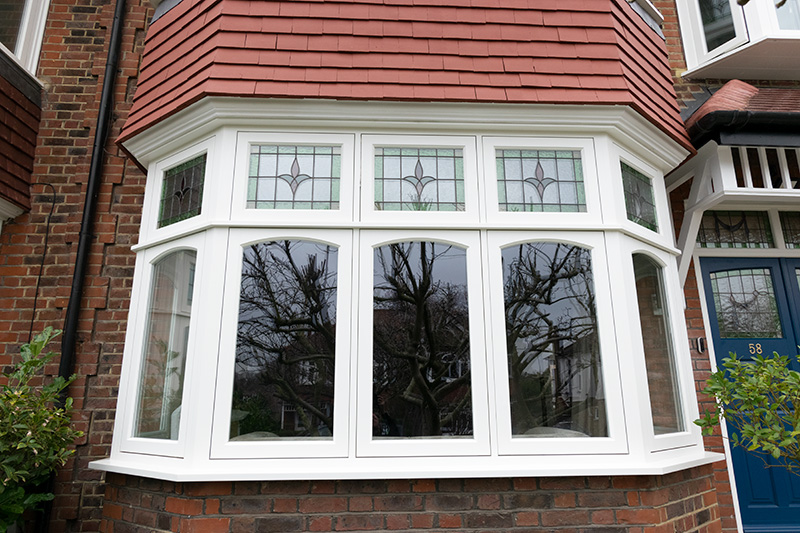Timber bay window with stained glass fan lights
